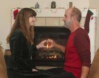 Ein Paar vor einem Kamin am Weihnachten Stockfotografie