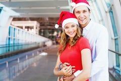Ein Paare tragendes santa& x27; s-Hüte lizenzfreie stockbilder