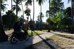 Ein Paarfahrmotorrad auf der Dorfstraße stockfoto