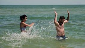 Ein Paarspiel in einem Meerwasser Sie zerschneiden sich Dann gibt junger Mann auf und fällt in das Wasser stock footage