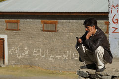 Ein pakistanischer Mann, der sein Mobiltelefon, Pakistan betrachtet Stockfotos