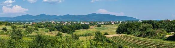 Ein Panorama von Hügeln mit Ackerland nahe dem Dorf auf dem Hintergrund der entfernten Berge Lizenzfreies Stockfoto
