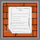 Ein Papierblatt zu Menü oder anderer Information über den Hintergrund einer Backsteinmauer Stockfoto