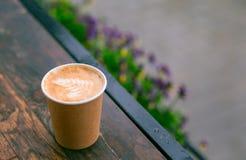 Ein Papiertasse kaffee mit Cappuccinoschaum-Kaffeekunst im Straßenhintergrund Kraftpapierschale lizenzfreie stockbilder