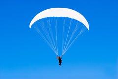 Ein paraplane, das hoch oben in den tiefen blauen Himmel fliegt Lizenzfreie Stockbilder