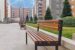 Ein Parkbankabschluß im städtischen Block der Stadt draußen Lizenzfreie Stockfotos