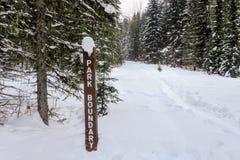 Ein Parkgrenzwegweiser entlang einem winterlichen Wanderweg in den schneebedeckten Wäldern provinziellen Parks Berg Fernie stockfotos