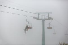Ein Passagier mit Fahrrad auf Sesselbahn im Nebel stockbild