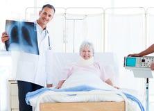 Ein Patient mit einer Stutzenklammer, die einen Röntgenstrahl betrachtet lizenzfreie stockbilder