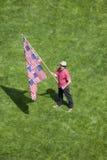 Ein patriotischer Mann mit einer US-Flagge, die von vielen US-Flaggen gemacht wird, steht allein in einem Rasen des grünen Grases Stockfoto