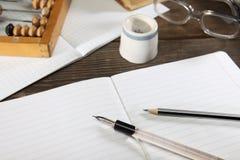 Ein Penholder mit einem Stift, ein Bleistift, ein Tintenfaß, Gläser und Abakus liegen auf einem alten Holztisch Ansicht von oben Lizenzfreies Stockbild