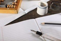 Ein Penholder mit einem Stift und ein einfacher Bleistift liegen auf einem offenen Notizbuch Ansicht von oben Nahaufnahme Lizenzfreie Stockfotografie