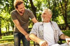 Ein Pensionär auf einem Rollstuhl und sein erwachsener Sohn gehen um den Park Sie sind glücklich und haben Spaß stockfotos
