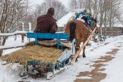 Ein Pferd trägt einen alten Mann in einem hölzernen Pferdeschlitten Stockbild