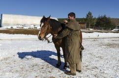 Ein Pferd und ein Mann vor Pferdestall Stockfotos