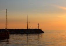 Ein Pier mit den Yachten nahe gelegen bei einem orange Sonnenuntergang auf dem Mediterranea Stockbild