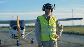 Ein Pilot betrachtet eine Kamera und oben steht auf einem flachen Hintergrund, Abschluss stock video