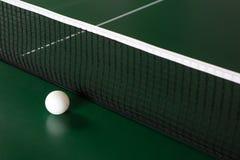 Ein Pingpong-Ball auf einer gr?nen Tabelle nahe bei dem Netz lizenzfreie stockbilder