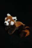 Ein Plüschspielzeug in Form eines roten Pandas auf einem schwarzen Hintergrund Lizenzfreies Stockfoto