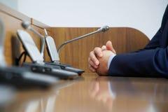Ein Politiker oder ein Geschäftsmann in einer Klage sitzt vor einem Mikrofon während einer Diskussion, einer Aufgabe oder einer D lizenzfreie stockfotografie