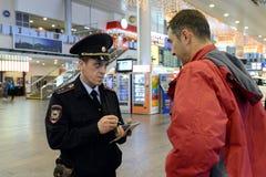 Ein Polizeibeamte überprüft die Informationsdatenbank des Bürgers am Eingang zum Moskau-Flughafen Stockfotografie