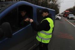 Ein Polizeibeamte steuert Verkehr auf der Autobahn nahe einer Straßensperre vor der Stadt von Kiew, Ukraine stockfoto