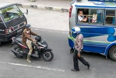 Ein Polizist, der dem Radfahrer auf verkehrsreicher Straße in Sumatra sich nähert Stockbilder