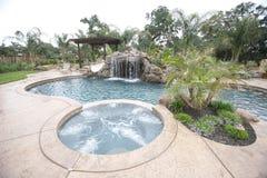 Ein Pool mit einem Wasserfall in einem Luxuxhinterhof Stockfotografie