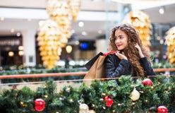 Ein Porträt der Jugendlichen mit Papiertüten im Einkaufszentrum am Weihnachten lizenzfreie stockfotografie