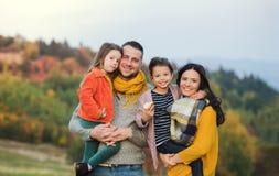 Ein Porträt der jungen Familie mit zwei kleinen Kindern in der Herbstnatur lizenzfreie stockbilder