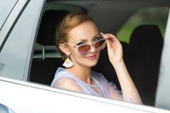Ein Porträt der schönen kaukasischen Frau mit dem blonden Haar, das durch Autofenster zur Kamera, lächelnd schaut lizenzfreies stockfoto