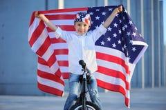 Ein Porträt des amerikanischen Jungen sitzend auf dem Fahrrad, das amerikanische Flagge hält Stockfotografie