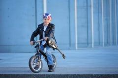 Ein Porträt des amerikanischen Jungen sitzend auf dem Fahrrad im Freien Stockfotos