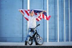 Ein Porträt des amerikanischen Jungen sitzend auf wellenartig bewegender amerikanischer Flagge des Fahrrades Lizenzfreie Stockfotografie