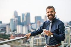 Ein Porträt des Geschäftsmannes mit dem Smartphone, der gegen London-Ansichtpanorama steht stockbild