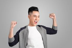 Ein Porträt des glücklichen aufgeregten jungen asiatischen Mannes mit Erfolg positiv stockfotos