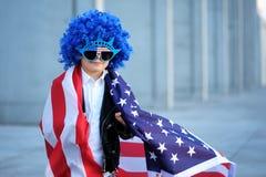 Ein Porträt des glücklichen Jungen in der blauen Perücke, die amerikanische Flagge hält Lizenzfreie Stockfotos