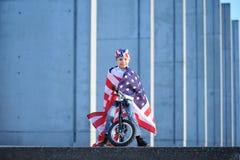 Ein Porträt des glücklichen Jungen sitzend auf Fahrrad wickelte amerikanische Flagge ein Stockfotografie