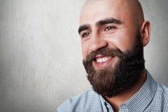 Ein Porträt des hübschen kahlen Mannes mit starkem Bart und des Schnurrbartes, der aufrichtiges Lächeln bei der Aufstellung gegen Stockfoto