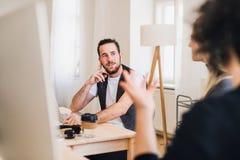 Ein Porträt des jungen Geschäftsmannes in einem modernen Büro, sprechend mit unerkennbaren Kollegen lizenzfreie stockbilder