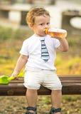 Ein Porträt des netten kleinen Jungen, der auf einer Parkbank sitzt und von einer Flasche mit einem Friedensstifter am Sommertag  Lizenzfreies Stockfoto