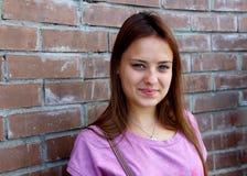 Ein Porträt des schönen Mädchens mit Backsteinmauerhintergrund Lizenzfreies Stockbild
