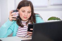 Ein Porträt des Schulmädchens, das Telefon verwendet Stockbild