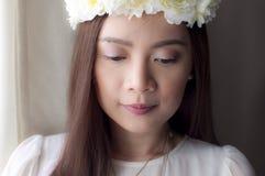 Ein Porträt einer Frau, die eine Blumenkrone trägt Stockbilder