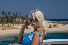 Ein Porträt einer jungen blonden Frau in der Sonnenbrille, auf einer dieser Yacht Segel in einem blauen Meer stehend lizenzfreies stockfoto