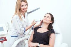 Ein Porträt eines attraktiven Dame Cosmetologist, der Laser-Gesichtsbehandlungsbehandlung zur Verfügung stellt stockfoto