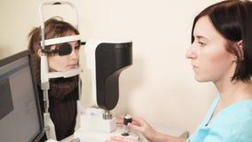 Ein Porträt eines Doktors, der einen Apparat für biomicroscopy der Retina gründete stock video