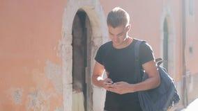 Ein Porträt eines hübschen surfenden Smartphone und des Gehens des jungen Mannes über die Stadt Sonniger Hintergrund Unscharfer H stock video