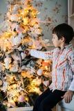 Ein Porträt eines Jungen, der nahe s-Tannenbaum sitzt stockfoto