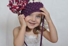 Ein Porträt eines lächelnden Babys in einer violetten Kappe Lizenzfreies Stockbild